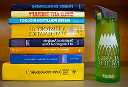Water bottle next to pile of books